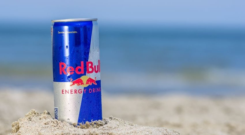 Photo of a can of Red Bull in the sand on the beach