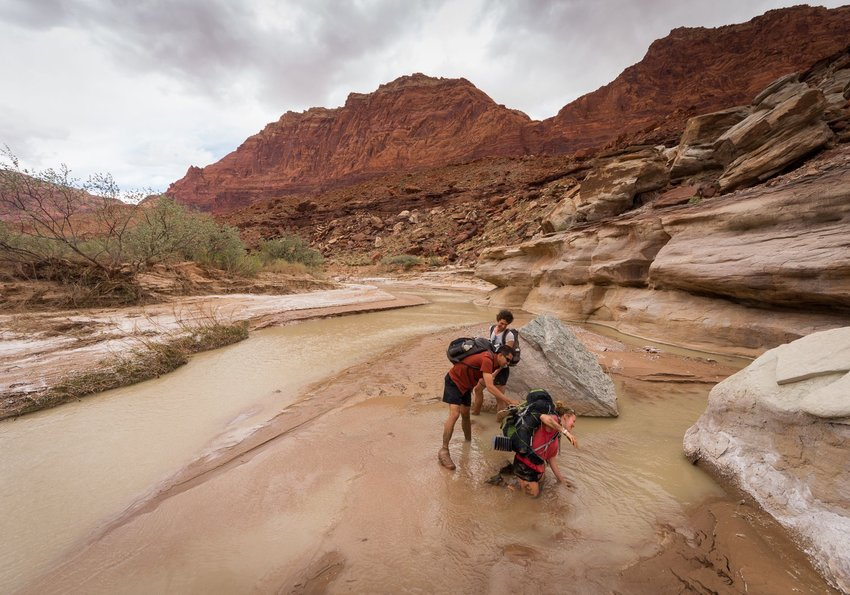 Photo of three people hiking in a desert and river landscape