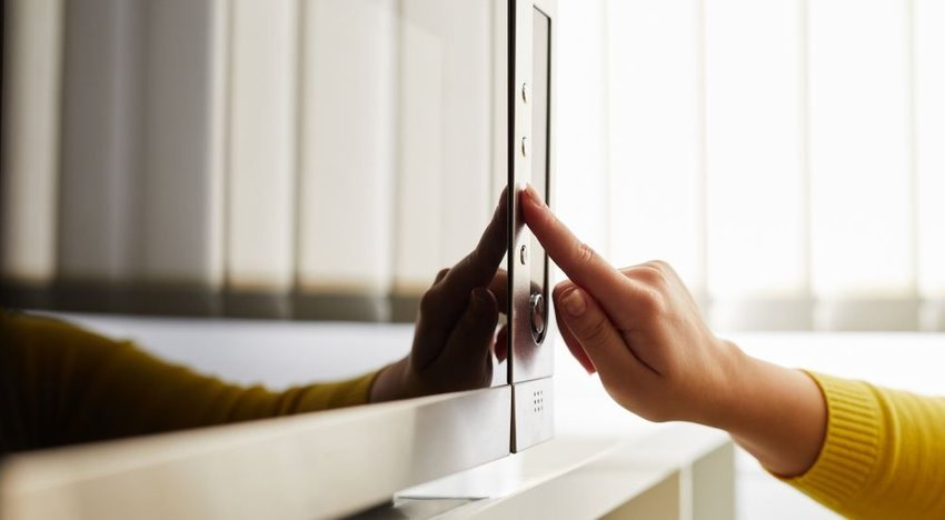 Photo of a hand pressing buttons on a microwave