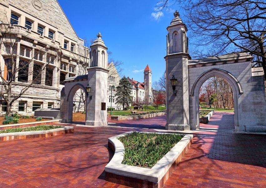 Arched stone gates on a red-brick walkway on the campus of Indiana University