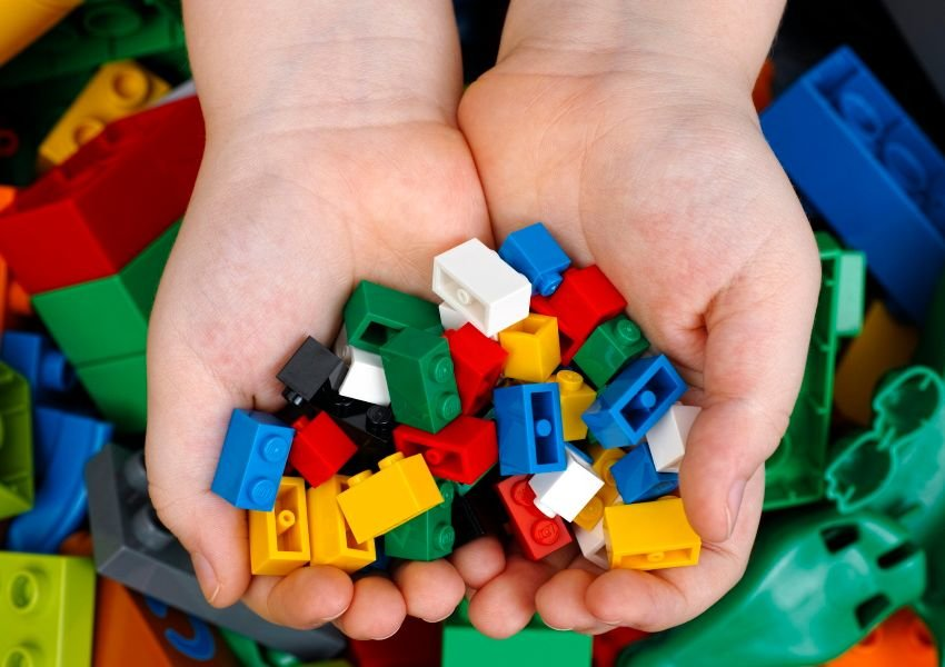 Photo of two hands holding a pile of Lego bricks in a variety of colors