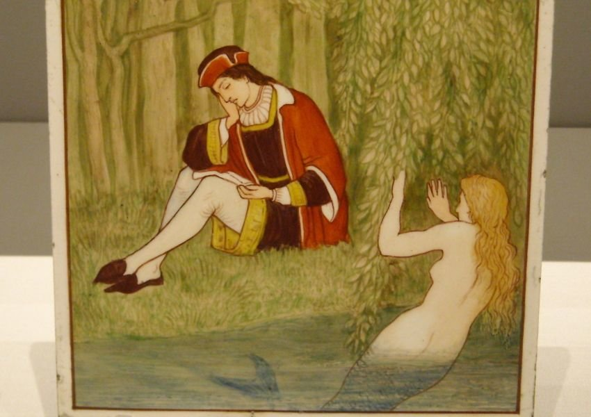 Photo of a painting of a mermaid in water looking at a man on land