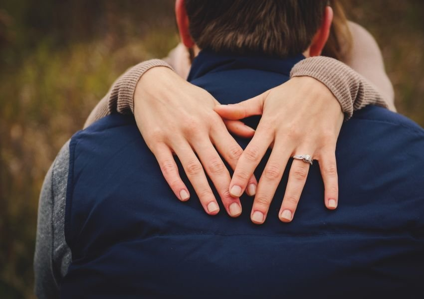 Woman with her hands around a mans shoulders, with a ring on her finger
