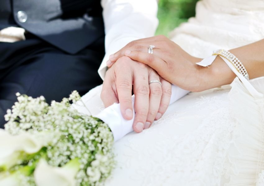 Close up of a man in a tuxedo and woman in a white dress, with their hands together and rings shown