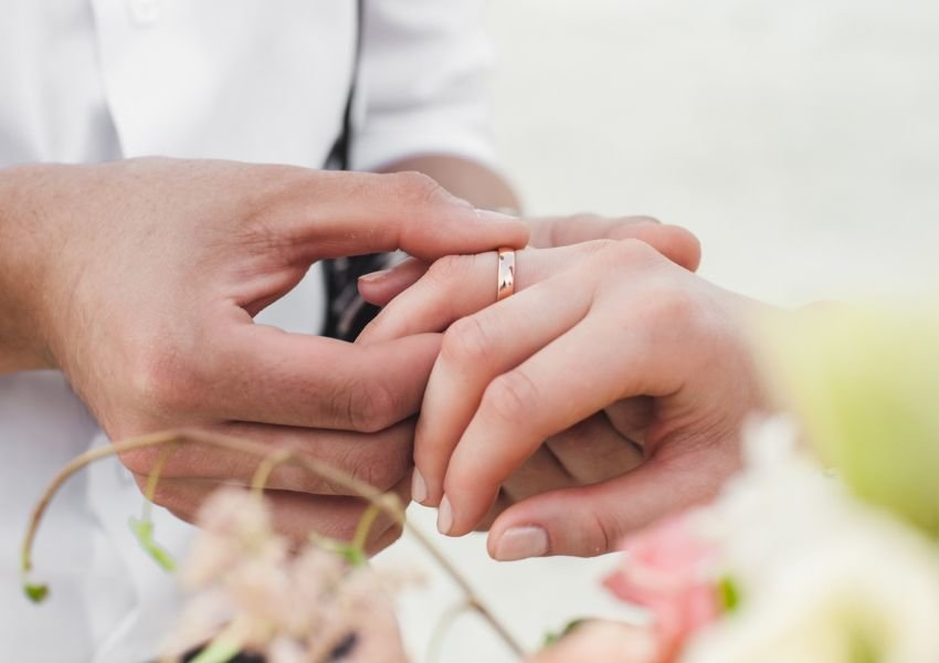 Man putting a rose gold ring on a woman's finger