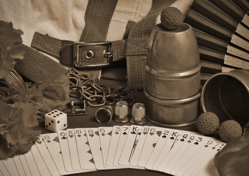 A deck of cards, dice, chains and thimbles in sepia tone