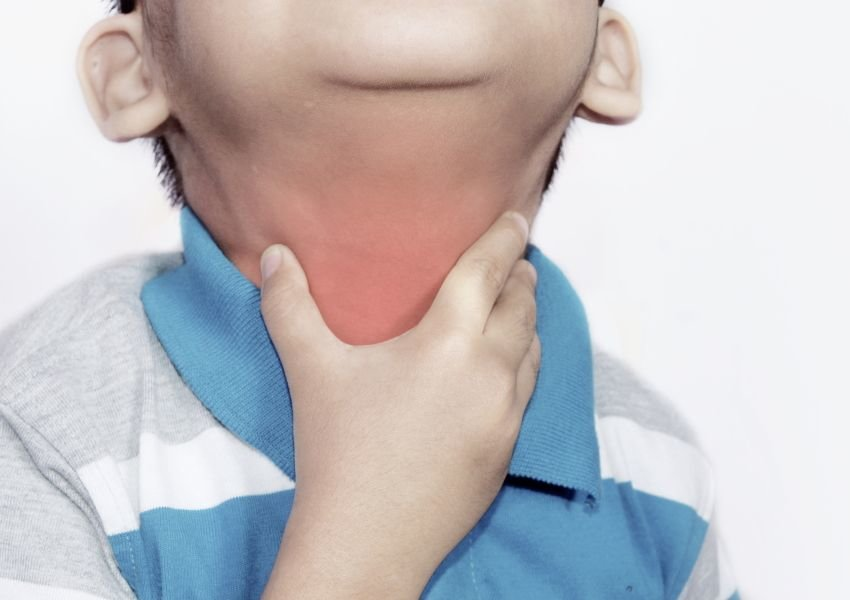 Photo of young boy grabbing enflamed neck