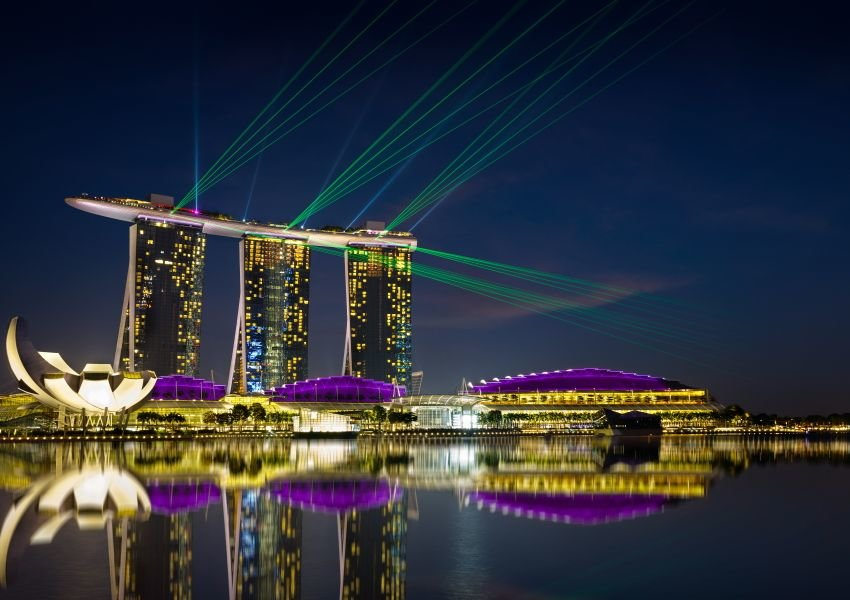 Marina Bay Sands building lit up and reflected in the water at night