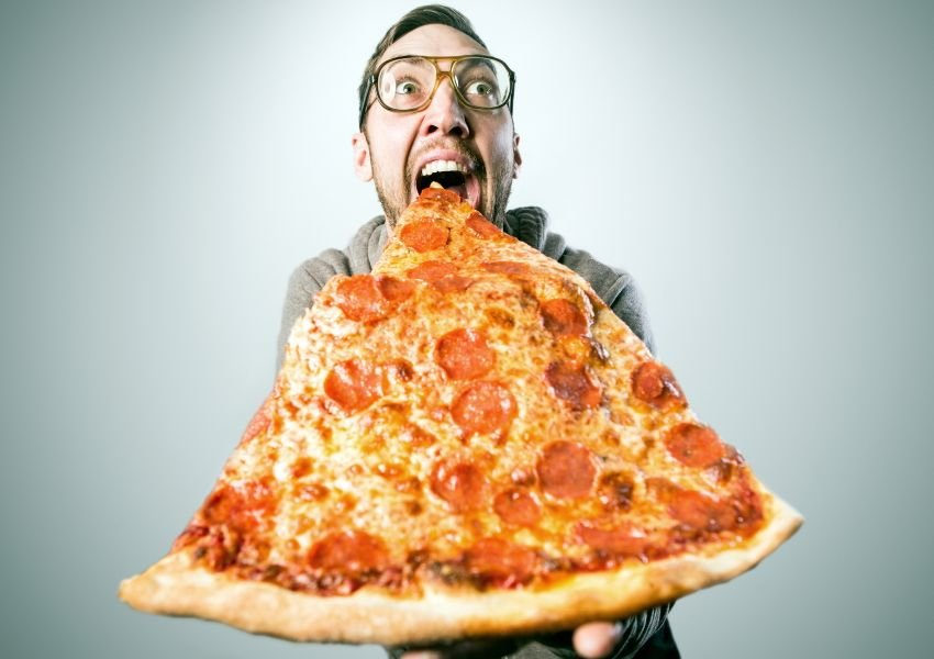 Man eating a giant slice of pizza