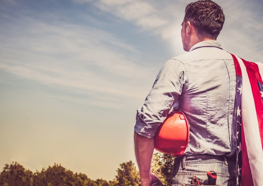 Photo of a man from behind holding a hard hat an American flag