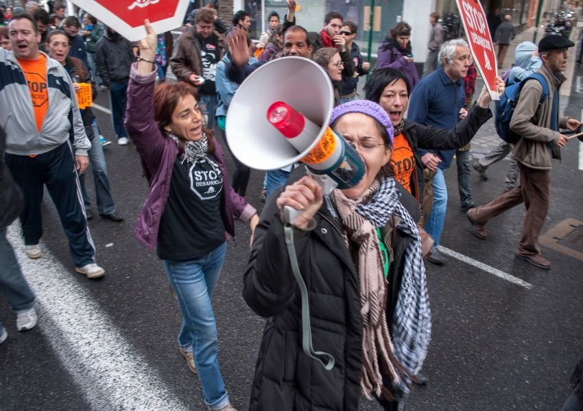 Photo of people striking in the street with signs and megaphones