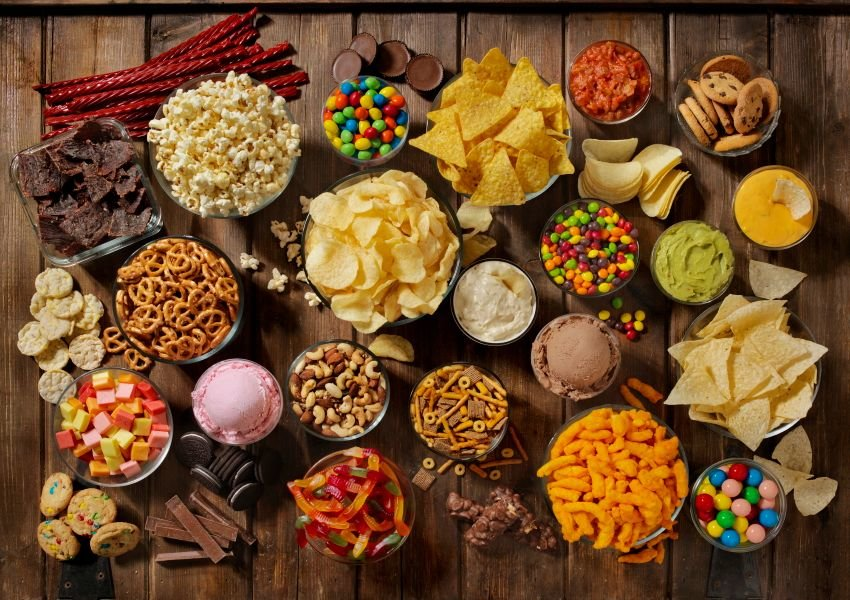 Aerial photo of various popular snacks including candy, popcorn, pretzels, chips, and ice cream
