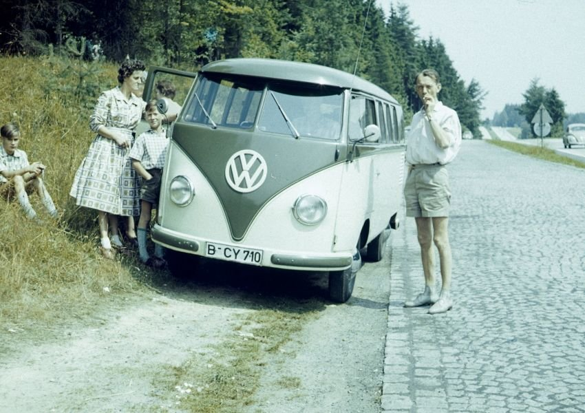 Vintage photo of a family standing next to a retro Volkswagen van
