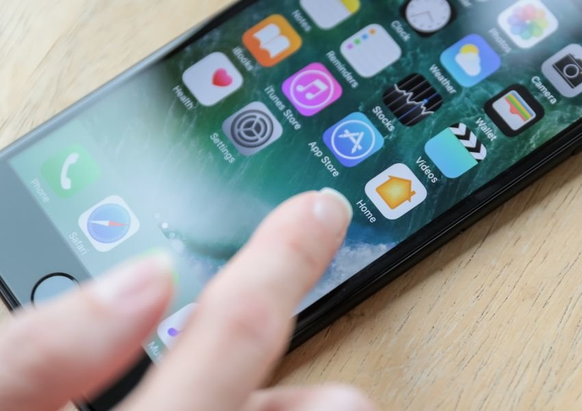 Close-up photo of a hand touching an iPhone screen