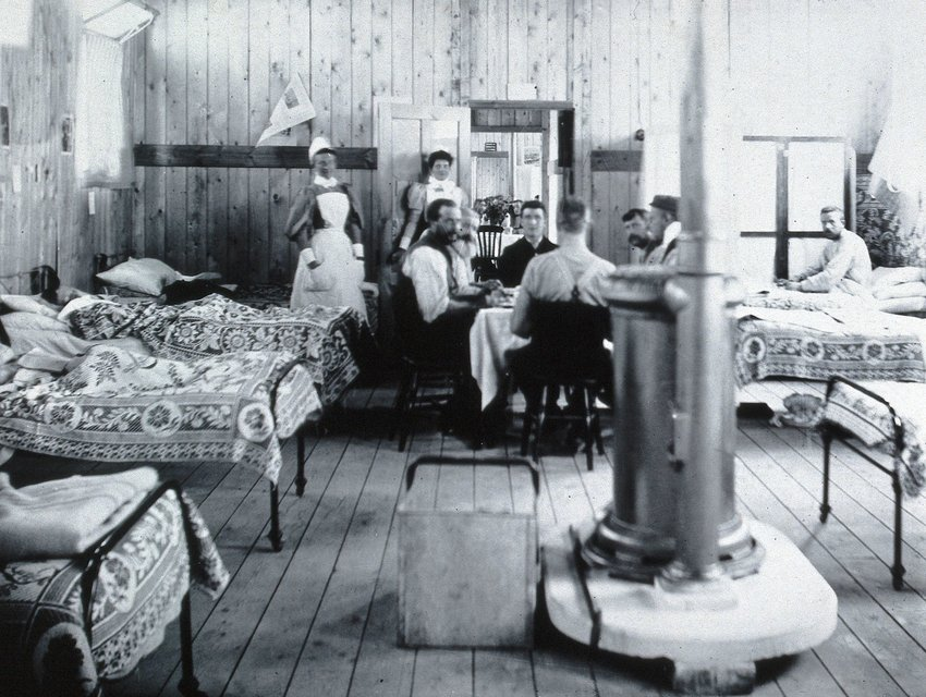 Black and white photo of an old, wood-paneled hospital room