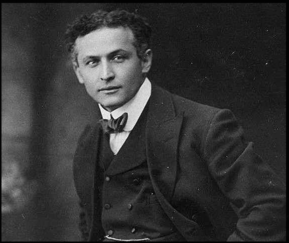 Harry Houdini in a suit, sitting for a photo