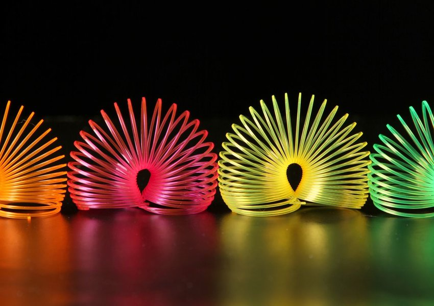 Photo of neon colored Slinky toys on a black background