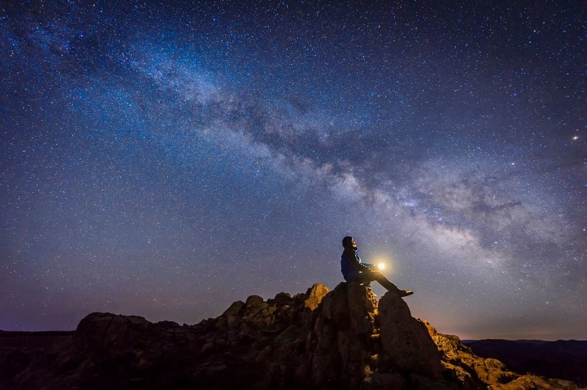 Photo of a person starting into a starry night sky