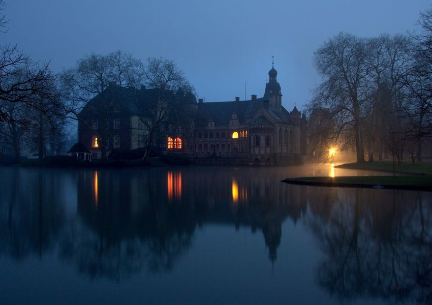 Photo of a dark, eerie castle surrounded by mist and a lake