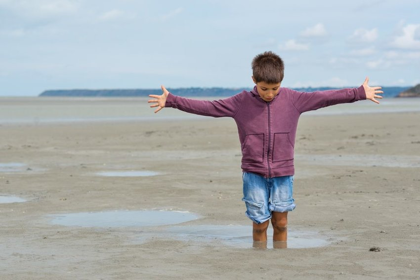 Young kid playing in quicksand at the beach