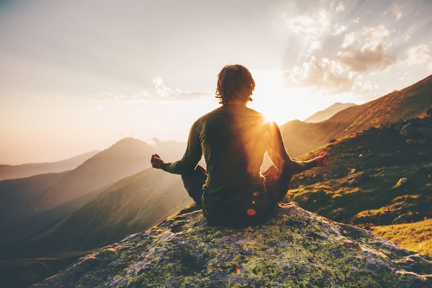 Photo of a person sitting in a meditation pose on top of a mountain