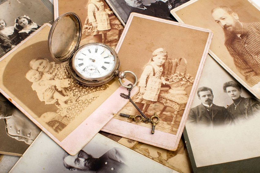 Photo of very old black and white photographs and an old-fashioned timepiece