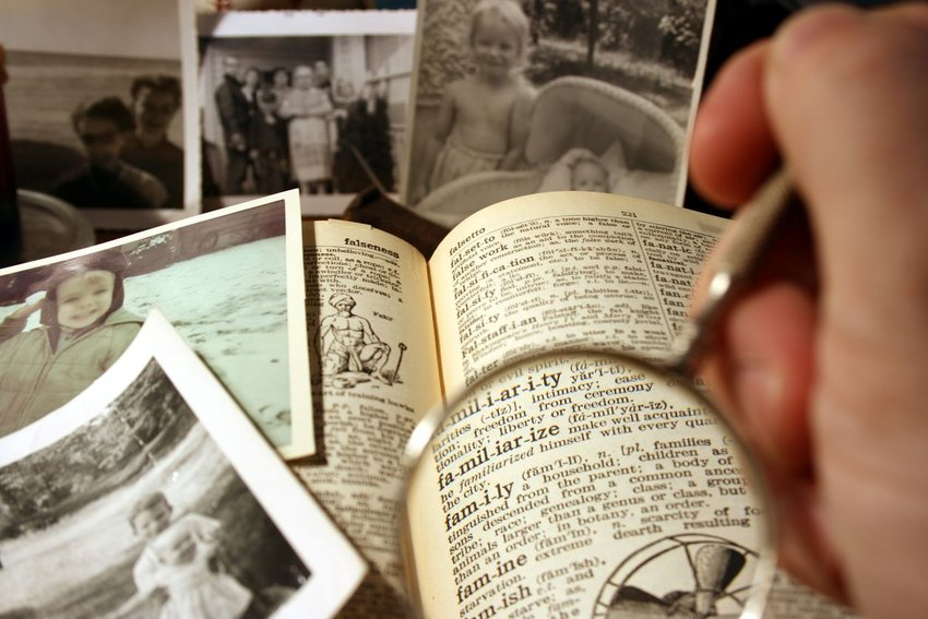 Photo of old photographs and books with a magnifying glass in the foreground