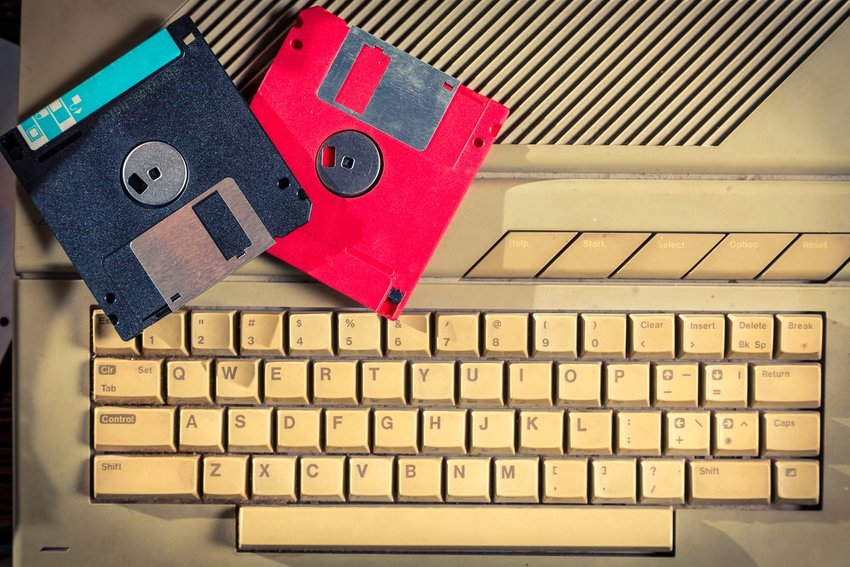 Photo of floppy disks sitting on an old, discolored computer keyboard