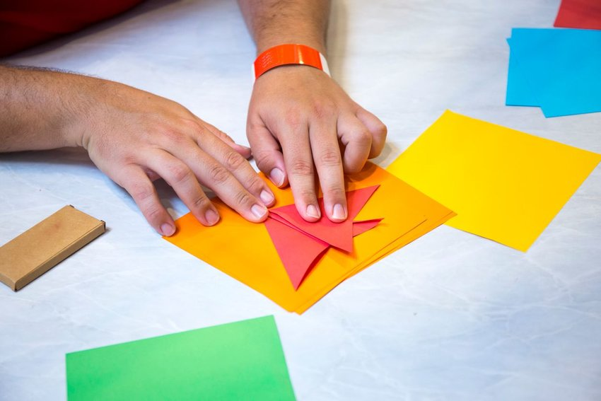Photo of a pair of hands folding brightly colored paper