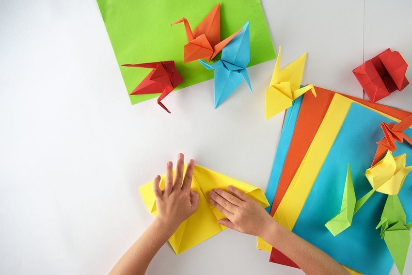Photo of a pair of hands folding brightly colored sheets of paper