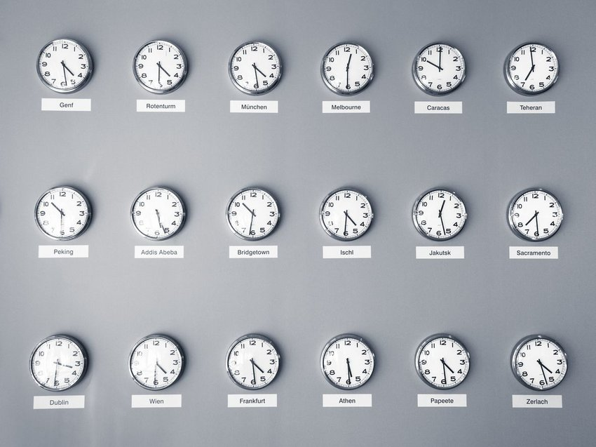 Photo of 18 clocks displaying times from different time zones on a wall