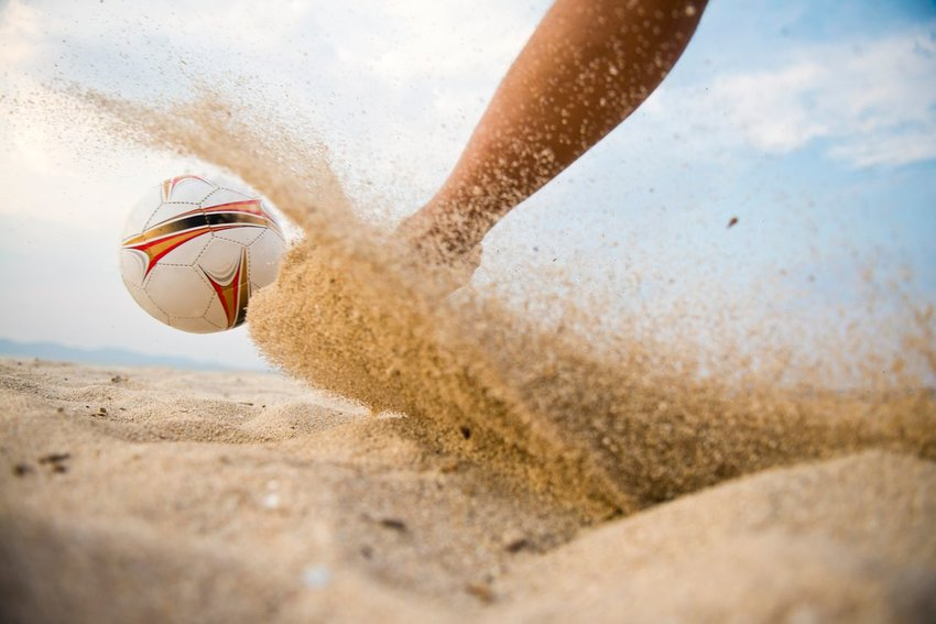 Photo of a volleyball on the beach kicking up sand