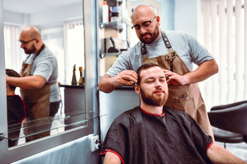Photo of a barber cutting the hair of a man who is smiling with his eyes closed