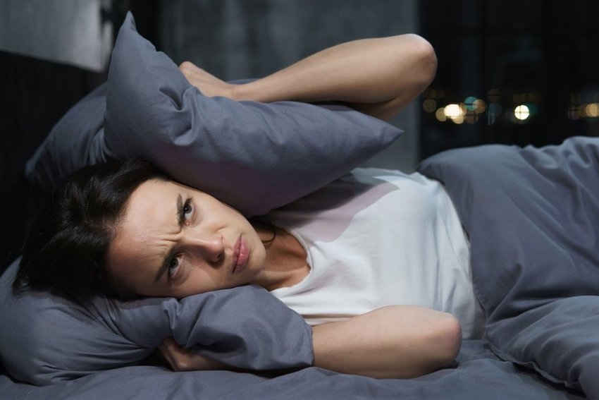 Photo of a woman lying in bed with a pillow over her ears