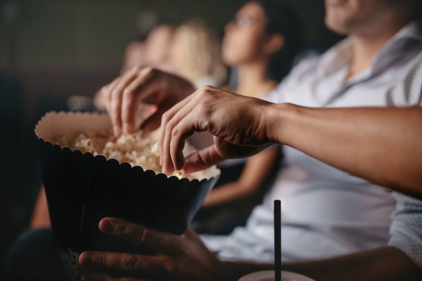 Photo of people grabbing popcorn out of a bucket in a movie theater