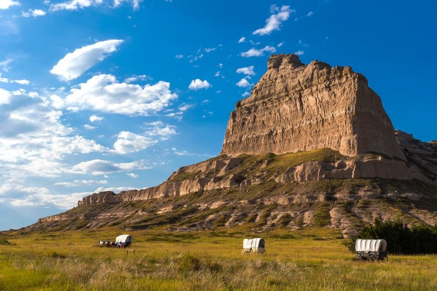 Photo of covered wagons traveling through the prairie with a mountain in the background