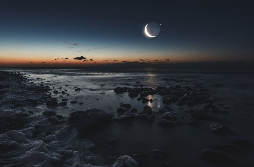 Photo of a the moon in a dark sky above a rocky coast