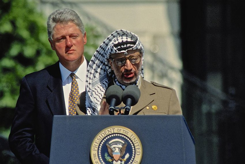 Photo of Yasser Arafat standing behind the presidential podium next to Bill Clinton