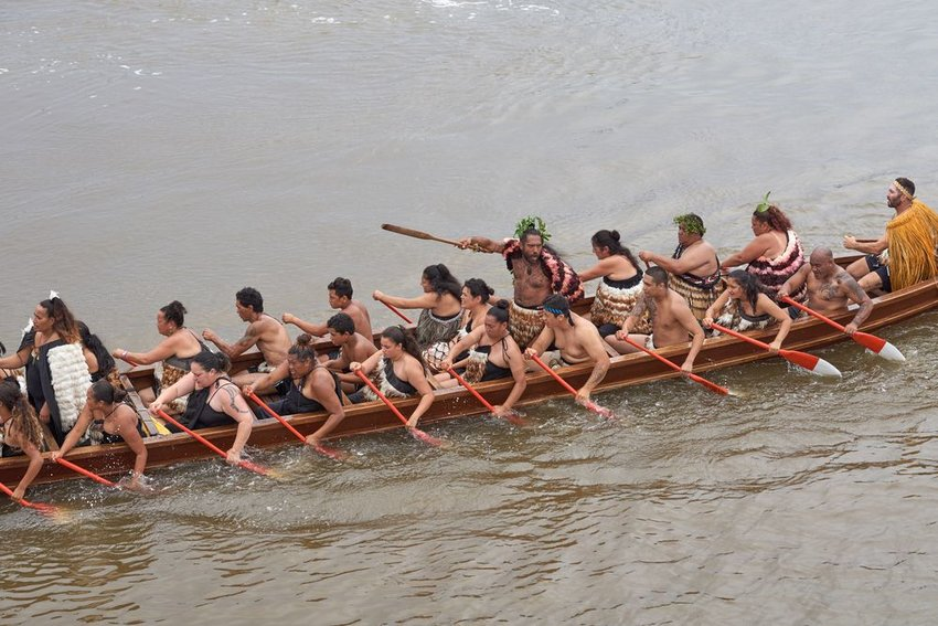 Photo of Polynesian people rowing a large canoe