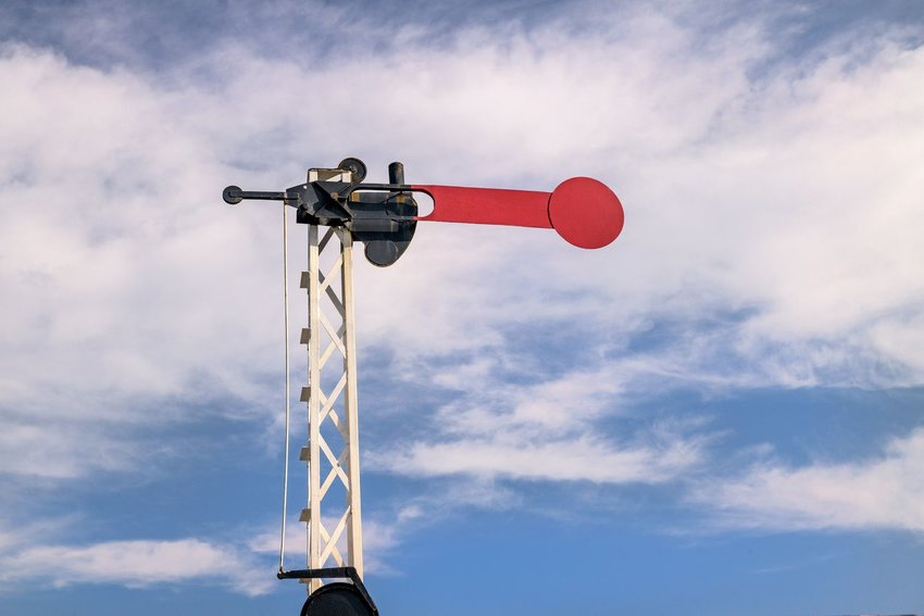 Red semaphore sign raised against blue sky and clouds, Ural, Russia
