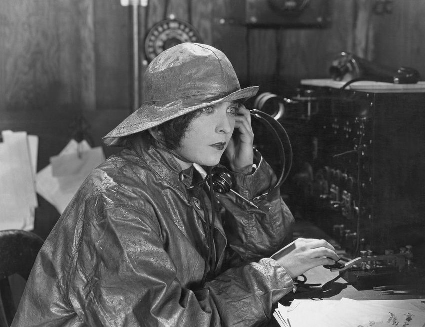 Woman operating antique telegraph, sending a message in Morse code