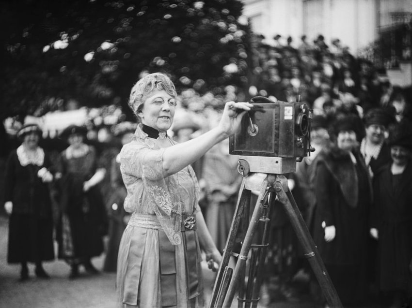 First Lady Florence Harding operating a newsreel in front of a crowd of journalists