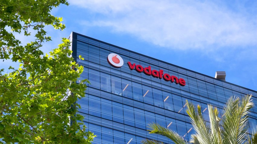 Vodafone building from a distance, showing large glass building and trees in foreground, Barcelona, Spain