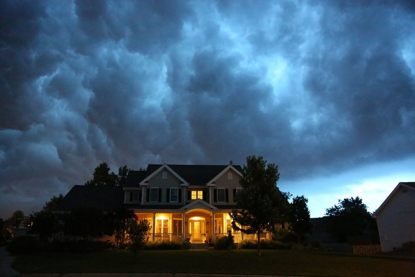 Photo of a two-story house with few lights on under an ominous cloudy sky