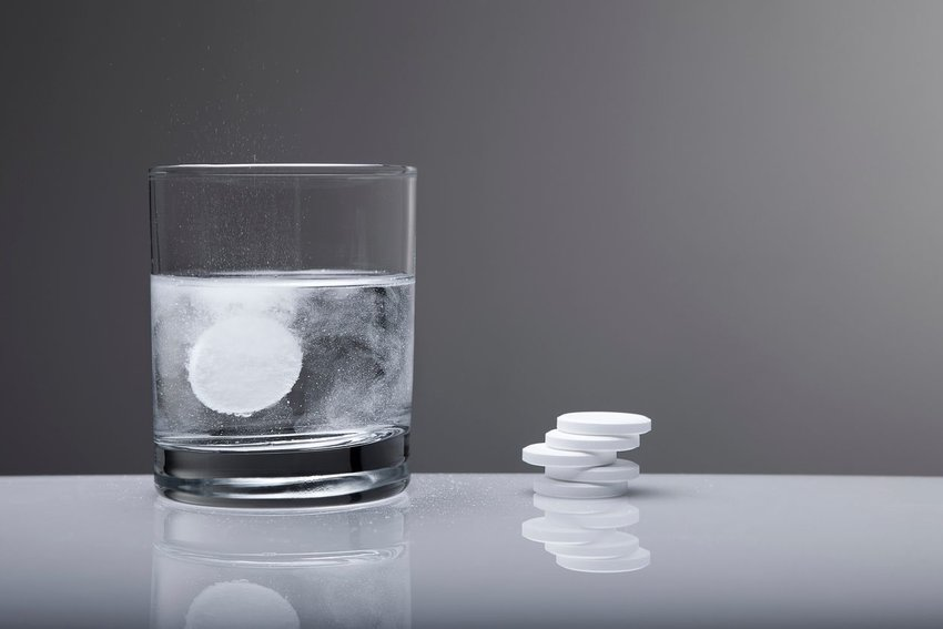 Photo of Alka Seltzer tablets with one dissolving in a glass of water