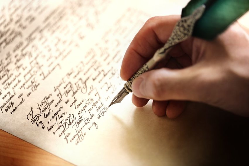 Photo of a hand writing on paper with a quill