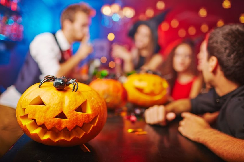 Photo of jack-o-lanterns on a bar with people partying in the background