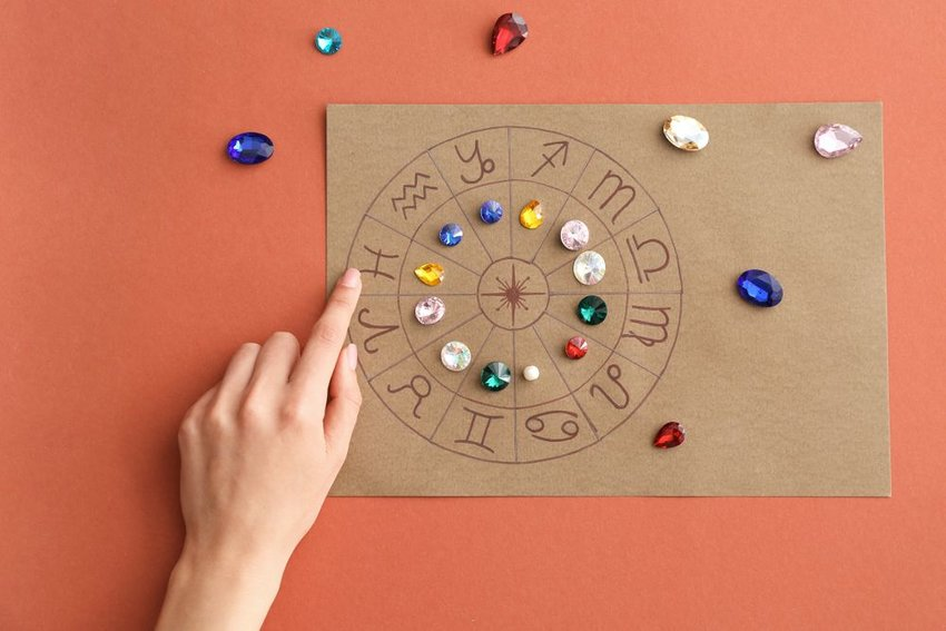 Woman's hand arranging birthstones on a zodiac chart against a red background
