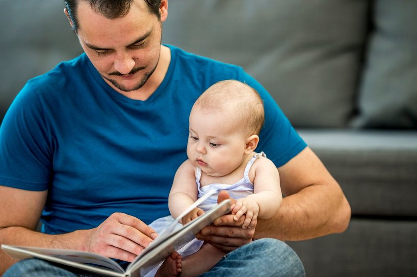 Father holding baby while reading book together