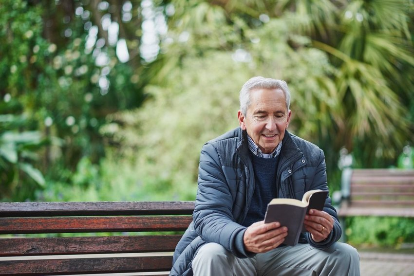 Older man reading a book while sitting in a park